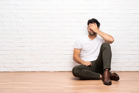Young man sitting on the floor covering eyes by hands. Do not want to see something