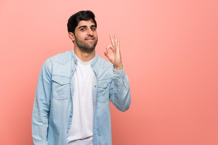 Young man over pink wall showing ok sign with fingers Imagens