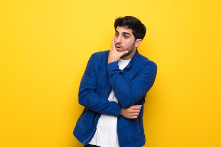Man with blue jacket over yellow wall surprised and shocked while looking right Reklamní fotografie