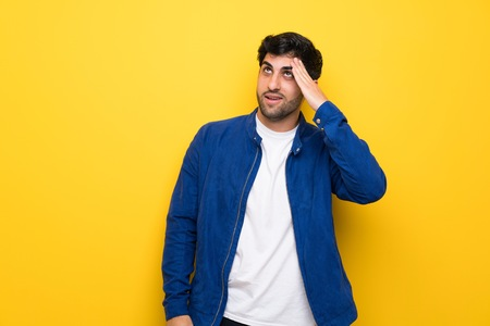 Man with blue jacket over yellow wall has just realized something and has intending the solution Stock Photo