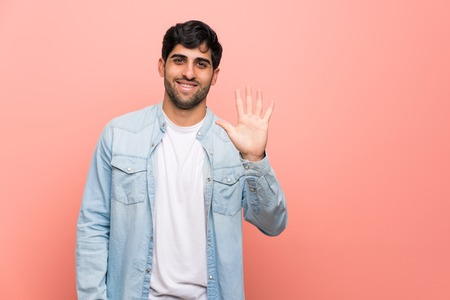 Young man over pink wall counting five with fingers