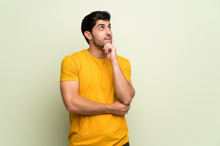 Young man over pink wall thinking an idea while looking up Imagens - 121941346