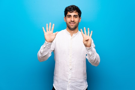 Young man over isolated blue wall counting nine with fingers