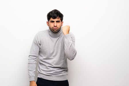 Young man over isolated white wall with angry gesture