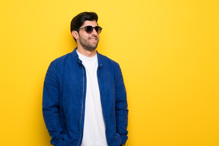 Man with blue jacket over yellow wall with glasses and smiling
