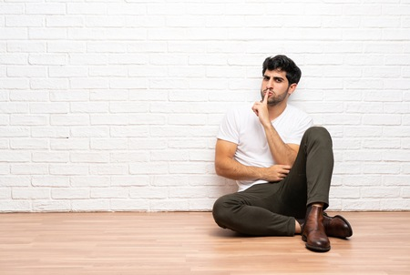 Young man sitting on the floor showing a sign of silence gesture putting finger in mouth