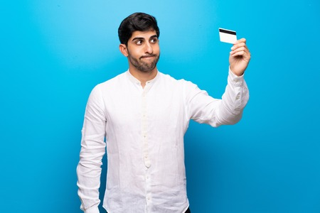 Young man over isolated blue wall taking a credit card without money