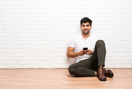 Young man sitting on the floor sending a message with the mobile