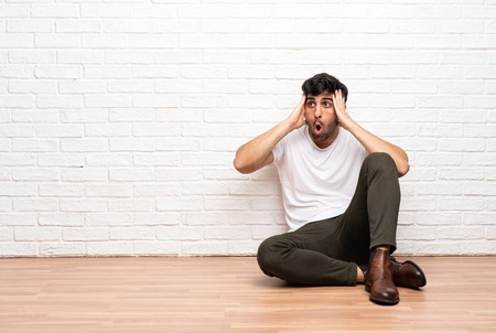 Young man sitting on the floor with surprise expression
