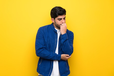 Man with blue jacket over yellow wall having doubts