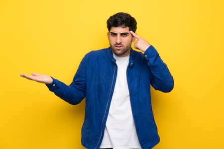 Man with blue jacket over yellow wall making the gesture of madness putting finger on the head