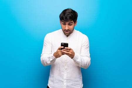Young man over isolated blue wall surprised with a mobile Stock Photo
