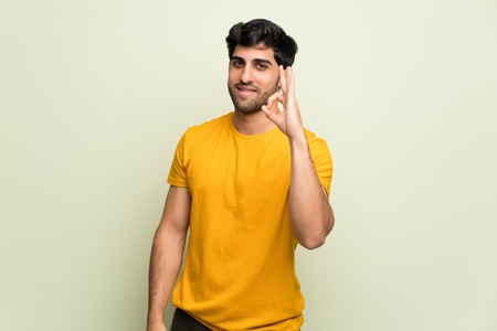 Young man over pink wall showing an ok sign with fingers