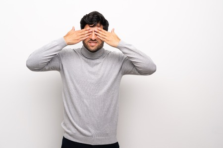 Young man over isolated white wall covering eyes by hands