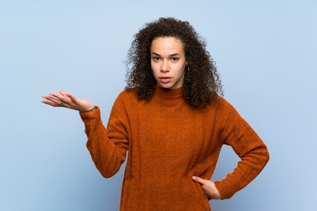 Dominican woman with curly hair making doubts gesture Imagens
