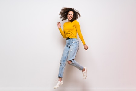 Dominican woman with curly hair jumping over isolated white background Imagens