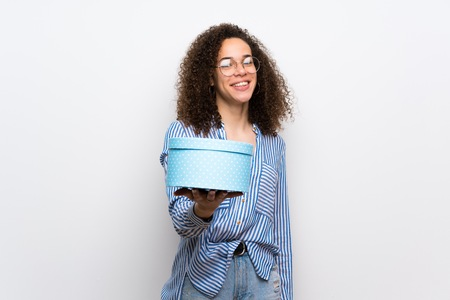 Dominican woman with striped shirt holding a gift in hands 免版税图像