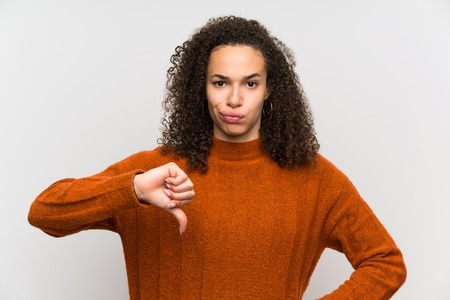 Dominican woman over isolated white wall showing thumb down sign