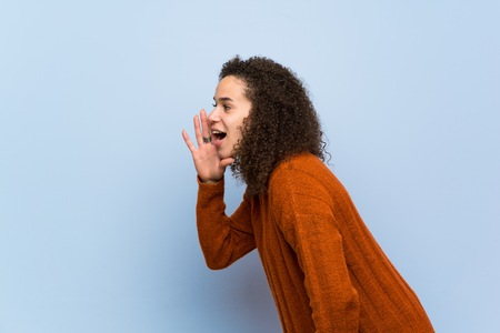 Dominican woman with curly hair shouting with mouth wide open to the lateral
