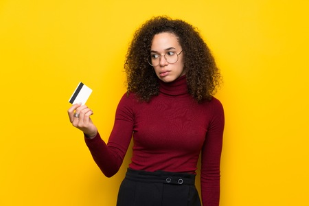 Dominican woman with turtleneck sweater taking a credit card without money 免版税图像