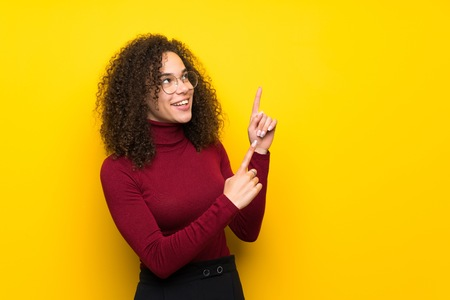 Dominican woman with turtleneck sweater pointing with the index finger and looking up Banque d'images