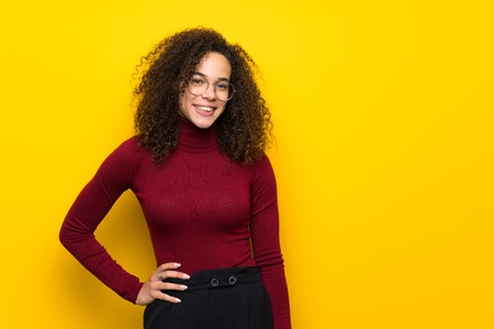 Dominican woman with turtleneck sweater posing with arms at hip and smiling 免版税图像