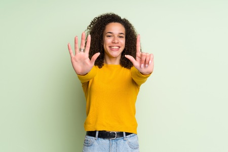 Dominican woman over isolated green background counting seven with fingers