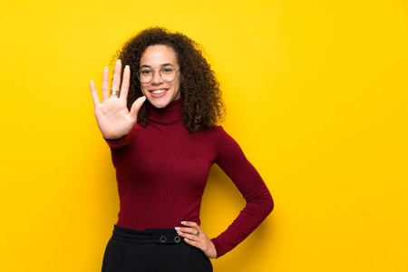 Dominican woman with turtleneck sweater counting five with fingers