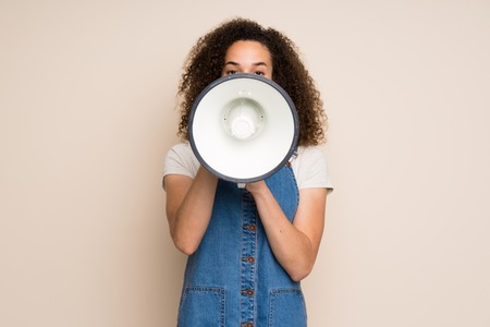 Dominican woman with overalls shouting through a megaphone