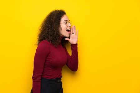 Dominican woman with turtleneck sweater shouting with mouth wide open to the lateral Stock Photo
