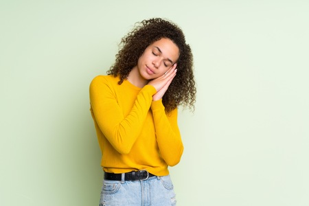 Dominican woman over isolated green background making sleep gesture in dorable expression