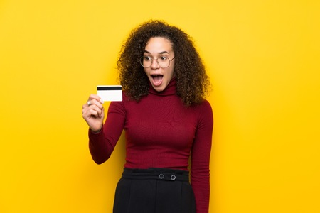 Dominican woman with turtleneck sweater holding a credit card and surprised