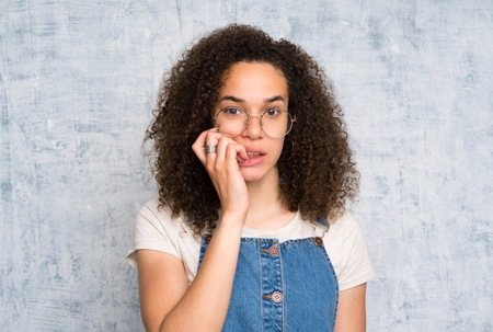 Dominican woman with overalls over grunge wall nervous and scared