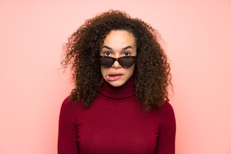 Dominican woman with turtleneck sweater having doubts and with confuse face expression