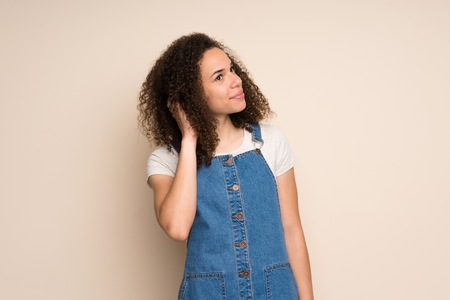 Dominican woman with overalls thinking an idea