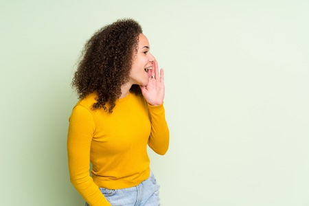 Dominican woman over isolated green background shouting with mouth wide open to the lateral