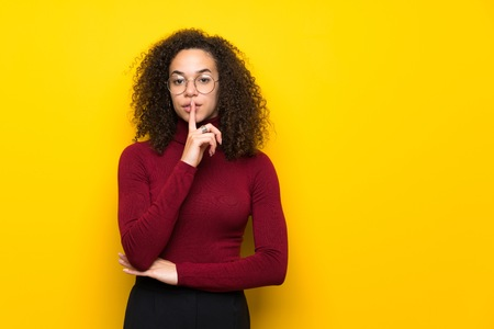 Dominican woman with turtleneck sweater showing a sign of silence gesture putting finger in mouth Imagens