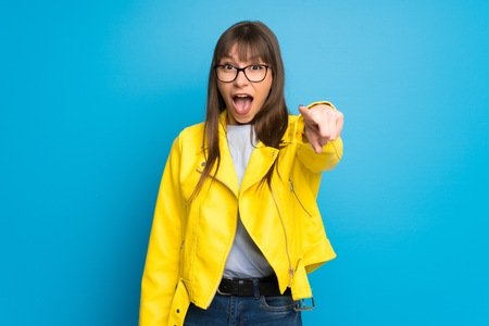 Young woman with yellow jacket on blue background surprised and pointing front Stok Fotoğraf