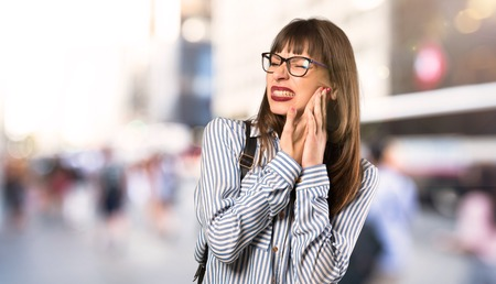 Woman with glasses with toothache at outdoors