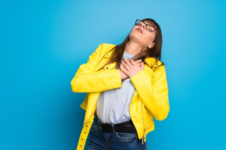 Young woman with yellow jacket on blue background having a pain in the heart Imagens