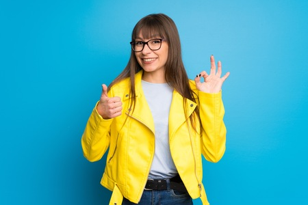 Young woman with yellow jacket on blue background showing ok sign with and giving a thumb up gesture