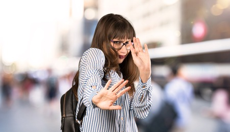 Woman with glasses nervous and scared stretching hands to the front at outdoors
