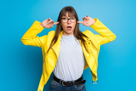 Young woman with yellow jacket on blue background covering both ears with hands Reklamní fotografie