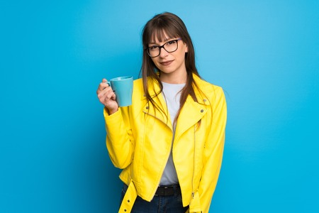 Young woman with yellow jacket on blue background holding a hot cup of coffee Imagens