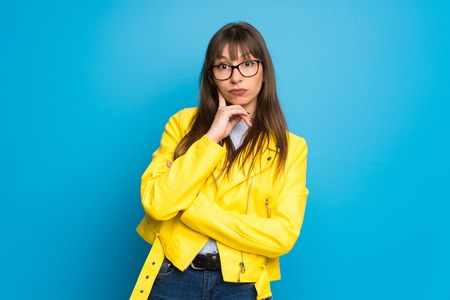 Young woman with yellow jacket on blue background thinking