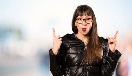 Woman with glasses pointing with the index finger a great idea at outdoors