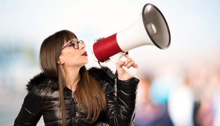 Woman with glasses shouting through a megaphone at outdoors