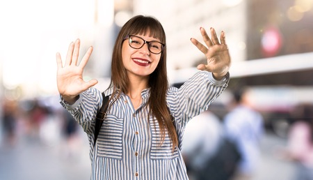 Donna con gli occhiali che conta dieci con le dita all'aperto Archivio Fotografico