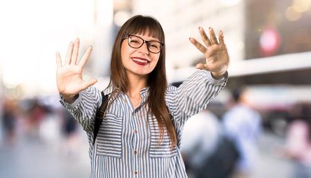 Vrouw met een bril die tien telt met vingers in de buitenlucht Stockfoto