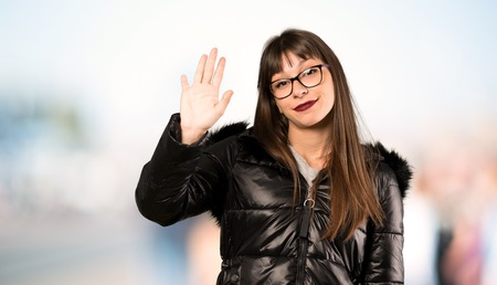 Woman with glasses saluting with hand with happy expression at outdoors Banco de Imagens